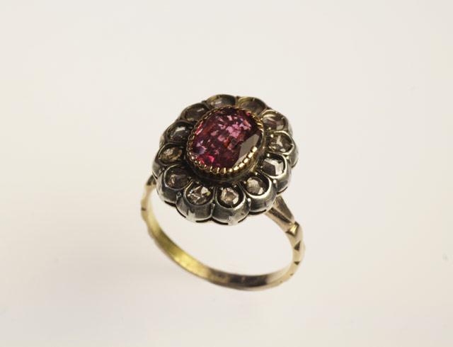"""Tipico anello di fidanzamento anni '50, con Granato centrale e rosette di diamante, tipologia a """"margherita""""."""